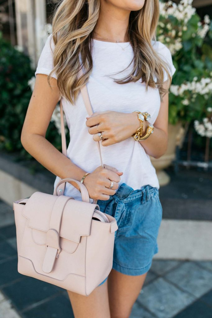 Pink bag with denim shorts and white tee
