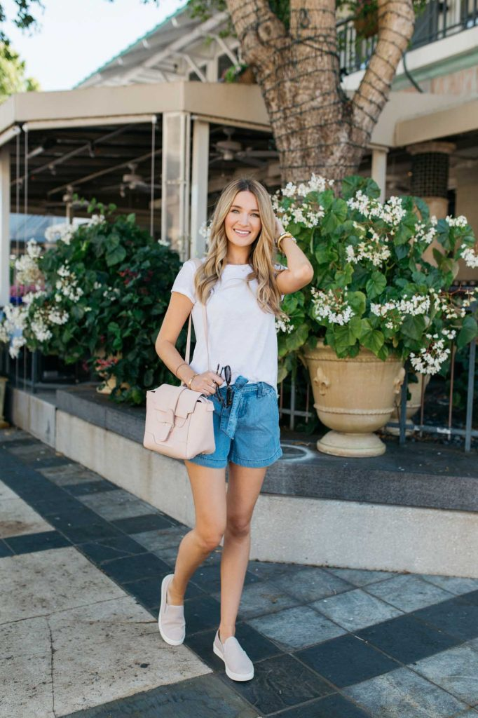 White top with chambray shorts and slide on sneakers